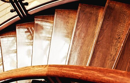 Part of an interior wooden staircase, in warm tones