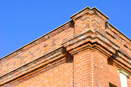 listed buildings: Part of the exterior of a red brick building against a vibrant blue summer sky