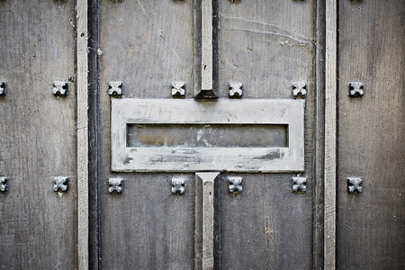An old metallic letterbox in a medieval wooden door