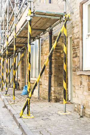 high visibility: Scaffolding poles outside an old English building with high visibility tape for safety