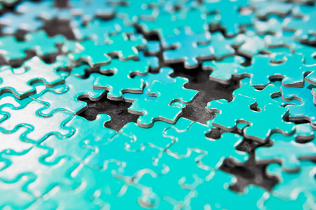 A plain blue jigsaw puzzle, partially completed with a shallow depth of field