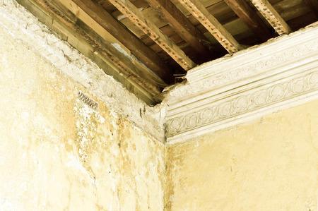 Een deel van een beschadigde interieur plafond met zichtbare hout