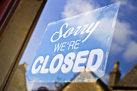 A closed sign hanging in the glass doorway of a shop in the UK