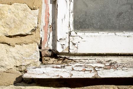 Een deel van de witte houten frame van een oud raam met peeling verf en verrot hout Stockfoto