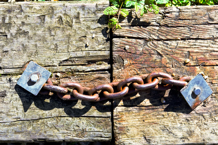 bridging the gaps: A rusty metal chain linking two wooden planks