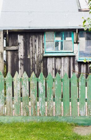 picket green: Part of a wooden out building with a green picket fence