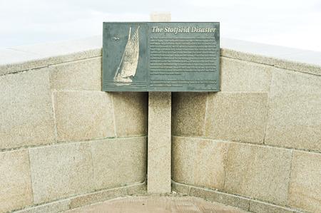 describing: LOSSIEMOUTN, SCOTLAND - OCTOBER 9 2015:  A stone sign describing the historic Stotfield diasaster in the area in the year 1806.
