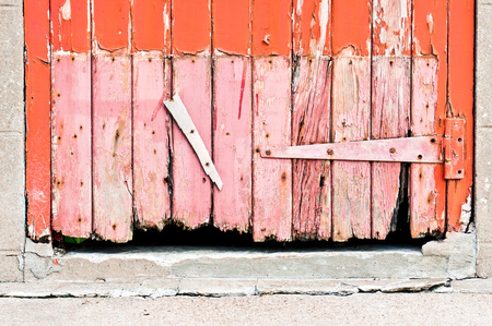 severely: The base of a red painted wooden door which is severely weathered