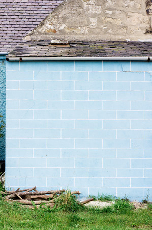 tiled wall: A blue tiled wall on the exterior of a single storey building