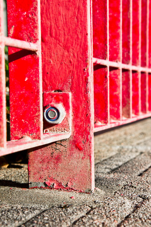 confined: Close up of part of a red metal fence Stock Photo