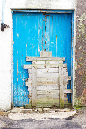 A blue door which has been boarded up by wooden planks