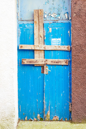 A weathered wooden door boarded up by planks