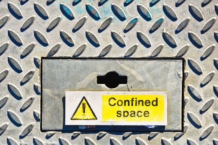 confined space: A yellow warning sign on a metal surface indicating a confined space