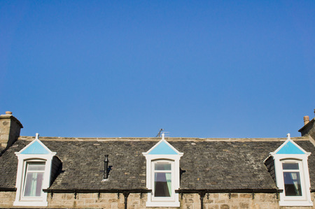 attic room: Windows of an attic room in a scottish house against a blue sky