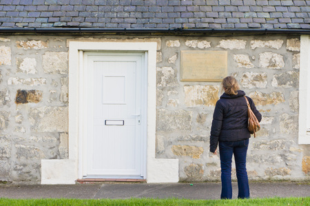 gb: LOSSIEMOUTH, SCOTLAND - OCTOBER 9 2015: A woman outside the birthplace home of Ramsay Macdonald, Britians first Labour party prime minister. Editorial