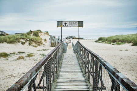 currents: The end of a wooden walkway at the beach in Lossiemout, Scotland with a warning sign about strong currents