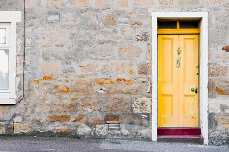 letting: A yellow wooden front door in a stone cottage in Scotland