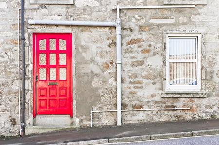 casa de campo: Una puerta roja en una casa de piedra en Escocia Foto de archivo