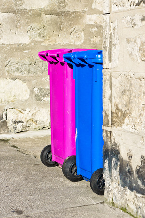 Two pink and blue plastic waste bins outside a stone cottage in Scotland