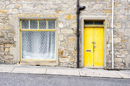 iron curtains: A stone building in Scotland with a yellow metal door and window