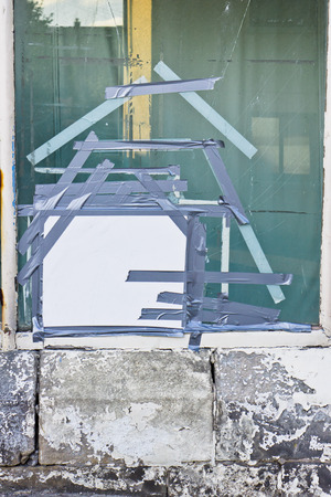 A window which has been broken and taped up