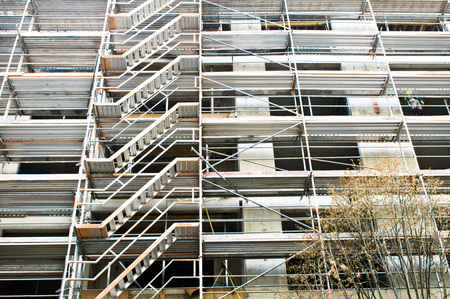 upkeep: Extensive scaffolding on the outside of a building during construction Stock Photo