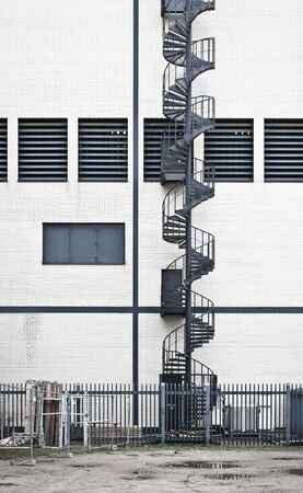 emergency stair: Part of a tall spiral staircase on the exterior of a modern building Stock Photo