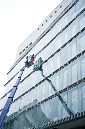 Workmen cleaning the outside of an office building Stok Fotoğraf