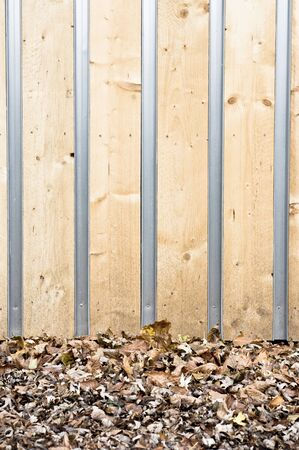 eco building: Part of the wall of a wooden eco building with fallen leaves on the ground