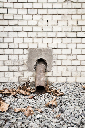 protruding: A rusty drainpipe protruding from an old brick wall Stock Photo