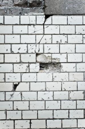 upkeep: Part of a damaged white brick wall