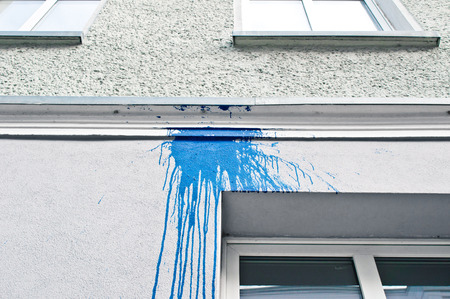 spilt: A stain from spilt blue paint on the exterior of a white building