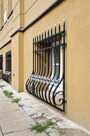 window bars: Wrought iron window bars on the exterior of an urban building at street level
