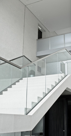 bannister: Part of a modern interior staircase with a glass bannister