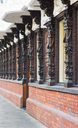 upkeep: A row of carved wooden columns on the front of a building in the UK Stock Photo