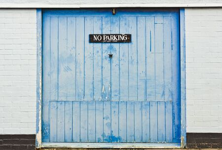 no  parking: A no parking warning notice on a blue wooden garage door Stock Photo