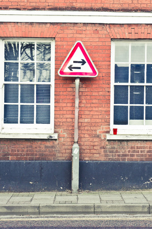 2 way: A warning sign for a 2 way street against a red brick wall building