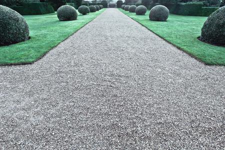 Een grindpad in een grote aangelegde tuin in het Verenigd Koninkrijk