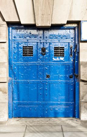 rejas de hierro: Una puerta azul medieval con barras de hierro forjado Foto de archivo