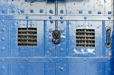 gaol: Part of a medieval blue door with wrought iron bars