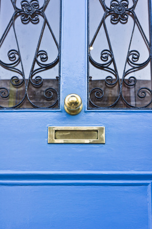handle bars: Part of a blue painted wooden front door with decorative bars and a brass handle and letterbox Stock Photo