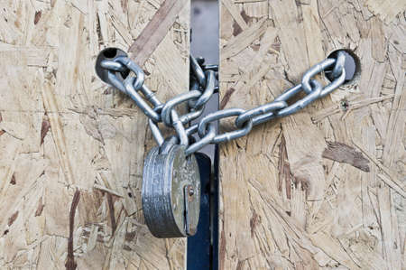 incarceration: A strong padlock and chain on a plywood gate