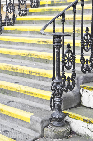 bannister: Part of a set of stone steps with metal railings at the entrance to a house Stock Photo