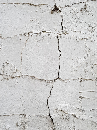 solid state: Part of a white painted stone wall with cracks
