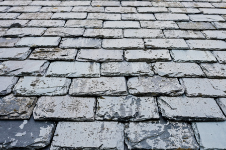 upkeep: Part of an olf weathered slate tile roof as a background