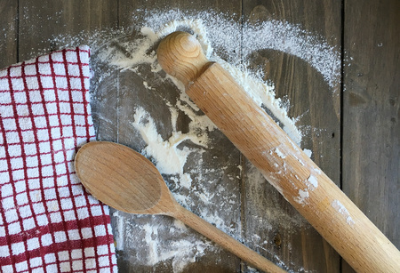 cooking implement: Wooden utensils and a tea towel on a flour covered wooden surface Stock Photo