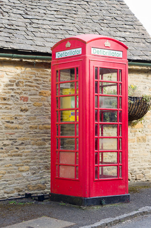 frequented: UPPER SLAUGHTER, UK - MARCH 25 2016: A classic british red phone box has been converted to a defibrillator facility in a village which is frequented by tourists.