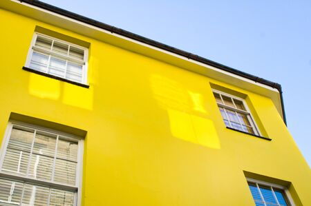 neighbours: Part of the exteior of a yellow townhouse in the UK Stock Photo