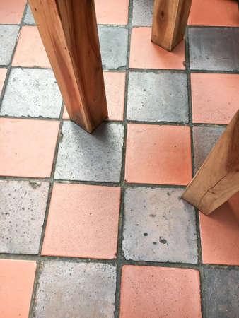 tiled floor: Wooden table legs on a tiled floor