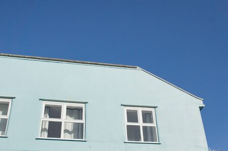 neighbours: Part of a bright blue building against a blue sky in the UK Stock Photo